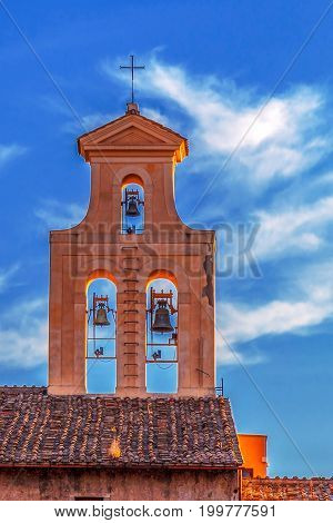 Old red bell tower with three bells in Rome Italy on a blue sky background.
