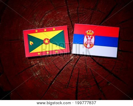 Grenada Flag With Serbian Flag On A Tree Stump Isolated