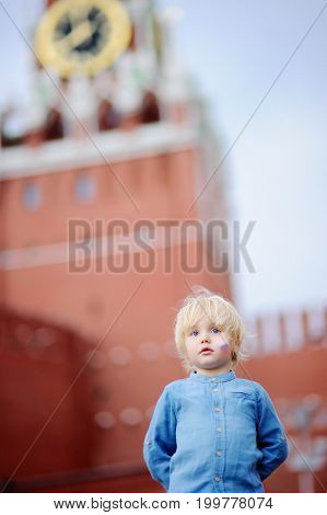 Cute Little Boy With Painted Russian Flag On Cheek With Spasskaya Tower (russia, Moscow) On Backgrou