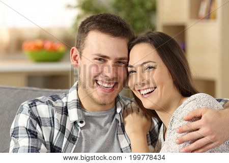 Happy couple with perfect teeth looking at camera sitting on a couch at home