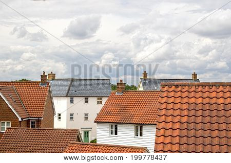Real estate. Suburban property roof tops on a modern contemporary housing estate. Mixed residential building types.