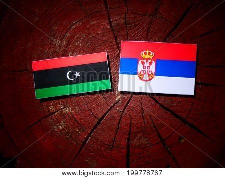Libyan Flag With Serbian Flag On A Tree Stump Isolated