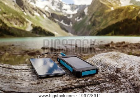 Battery Solar Energy Device On The Background Of Beautiful Mountain Scenery.