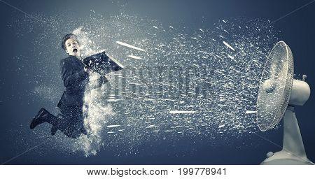 Businessman flying beside a powerful fan fan causing snow.