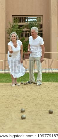 Portrait of a senior couple throwing balls in sand