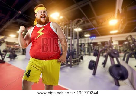 Thick fat funny man winner smiles in sports clothes in the gym.