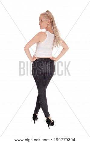 A gorgeous slim young woman in black jeans and white t-shirt standing from the back looking over her shoulder isolated for white background