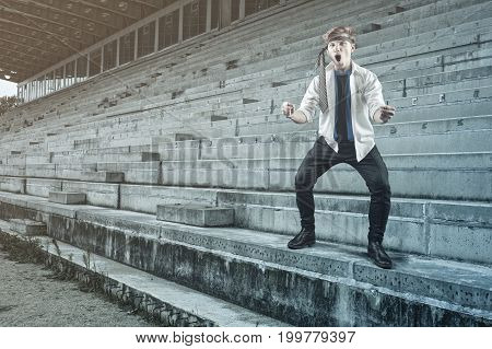 Businessman watching the game alone on stadium and celebrate the goal.