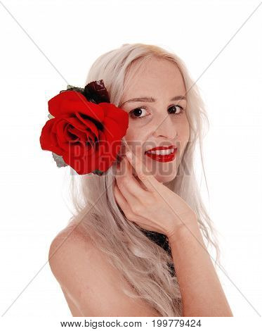 A lovely young blond woman standing in profile holding a big red rose to her head with red lips isolated for white background
