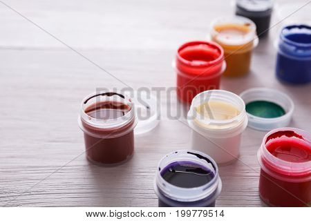 Artist workplace. Set of color gouache jars and acrylic paints on white wooden background with copy space