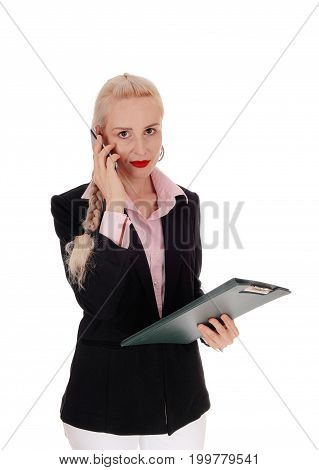 A pretty businesswoman talking on her cell phone in a black jacket holding the notepad in her hand isolated for white background
