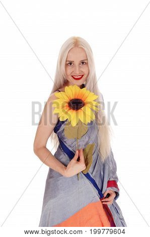A gorgeous young blond woman in an east Indian dress smiling and holding a sunflower isolated for white background