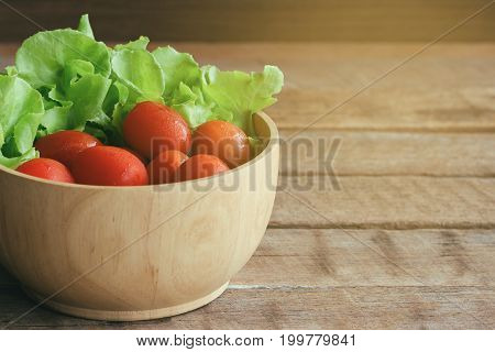 Fresh tomato and lettuce in wood bowl put on wood table. Side view close up of tomato and green oak lettuce with copy space for background. Fresh green oak lettuce and tomato prepare for cooking.