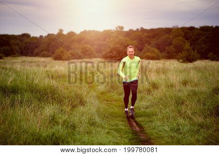 Fit muscular man jogging on a rural trail at sunset through grassland wearing sportswear in an active lifestyle concept
