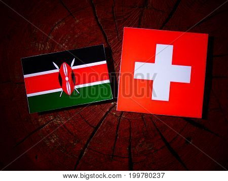 Kenyan Flag With Swiss Flag On A Tree Stump Isolated