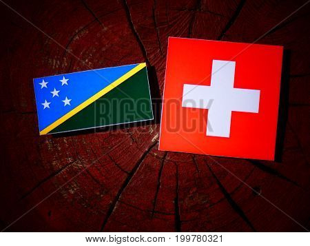 Solomon Islands Flag With Swiss Flag On A Tree Stump Isolated