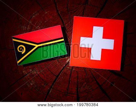 Vanuatu Flag With Swiss Flag On A Tree Stump Isolated