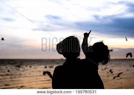 The girl is pointing to the sky on her mom holding in silhouette concept.