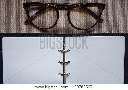 Note book with blank paper and glasses.