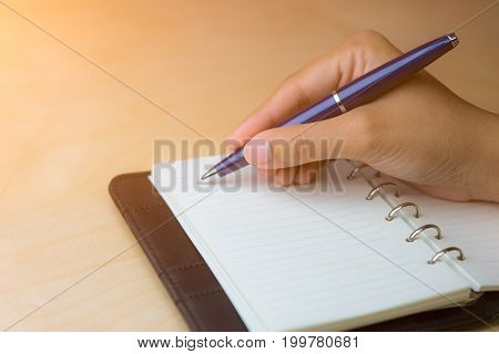 Take note on notebook by blue ball pen.