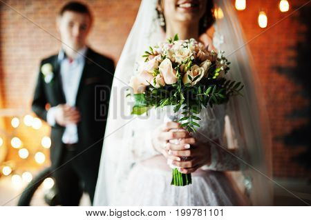 Close-up Photo Of A Bouquet In Bride's Hands. Groom In The Background.