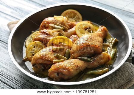 Delicious chicken drumsticks with lemon in frying pan on wooden table