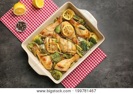 Delicious roasted chicken drumsticks with lemon and vegetables in baking dish on table
