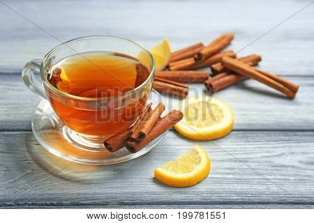 Cup with aromatic hot cinnamon tea and lemon on wooden table