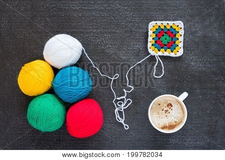 Balls of multicoloured yarn, crocheted motif and a cup of coffee on grunge black background.