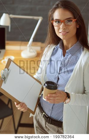 Young woman standing near desk with laptop holding folder and cup of coffee. Workplace. Business Woman.