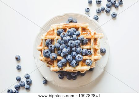 Top View Of Plate Of Tasty Stacked Waffles With Blueberries