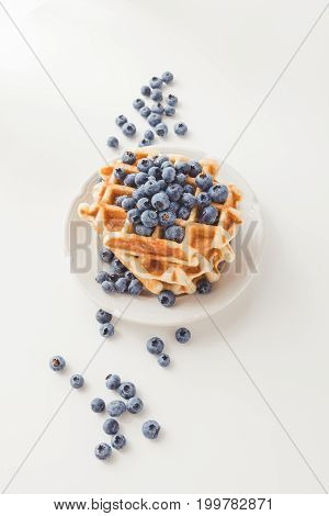 plate of delicious waffles with fresh blueberries