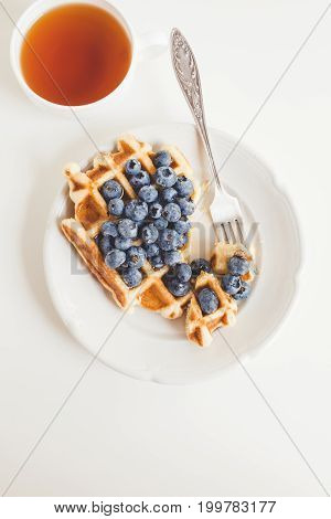 Waffle With Blueberries And Cup Of Tea For Breakfast