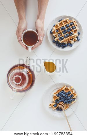 Top View Of Delicious Breakfast Of Waffles And Tea In Female Hands