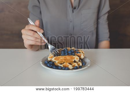 Cropped Shot Of Woman Eating Waffles With Blueberries For Breakfast