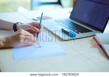 Young woman sitting at the desk with instruments, plan and laptop. Young woman