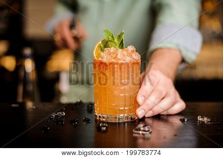 Bartender finished decorating his cocktail with mint and orange slice