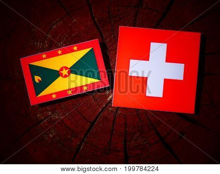 Grenada Flag With Swiss Flag On A Tree Stump Isolated