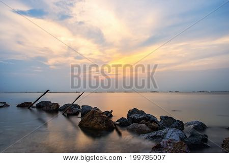Sunset on the rocky Maine coast with a beautiful blue and orange sky. The pink granite rocks are lit by the setting sun.