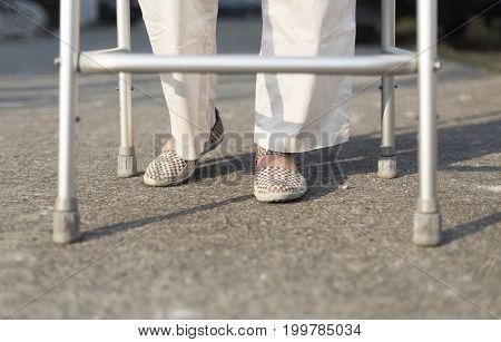 senior woman using a walker cross street.