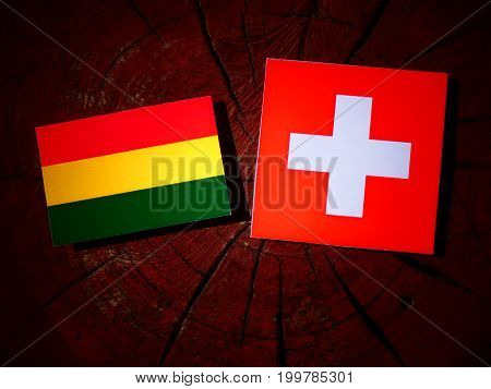 Bolivian Flag With Swiss Flag On A Tree Stump Isolated