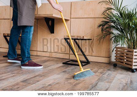 Worker Cleaning Floor With Broom