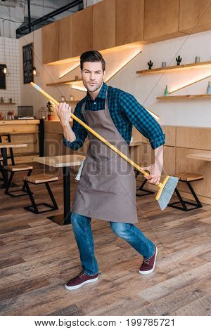 Man Having Fun With Broom In Cafe