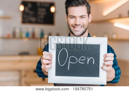 Barista Showing Chalkboard With Open Word