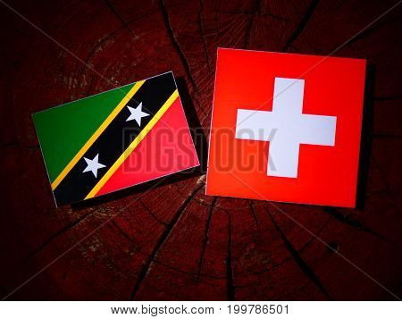 Saint Kitts And Nevis Flag With Swiss Flag On A Tree Stump Isolated