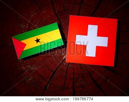 Sao Tome And Principe Flag With Swiss Flag On A Tree Stump Isolated