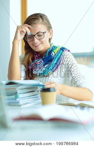 Young woman sitting at a desk among books. Student