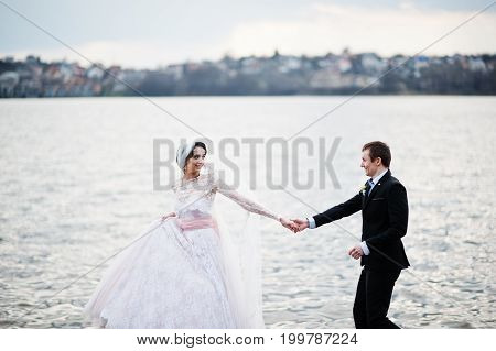 Newly Married Couple Walking And Posing On The Lakeside On Their Wedding Day.