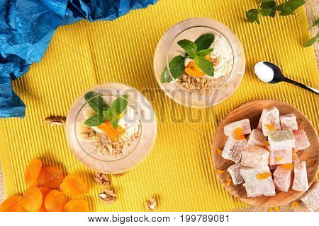 Top view of two banana smoothies in a huge glasses with Turkish Delight, dried apricots, walnuts and spoon on multi-colored background. Healthy smoothie with sweets. and fruits.