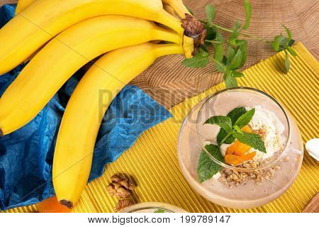 Close-up of a dessert glass full of fruit smoothie from ice cream, bananas, dried apricots and leaves of mint and a branch with bananas on a bright yellow background. Banana milkshake with fruits.